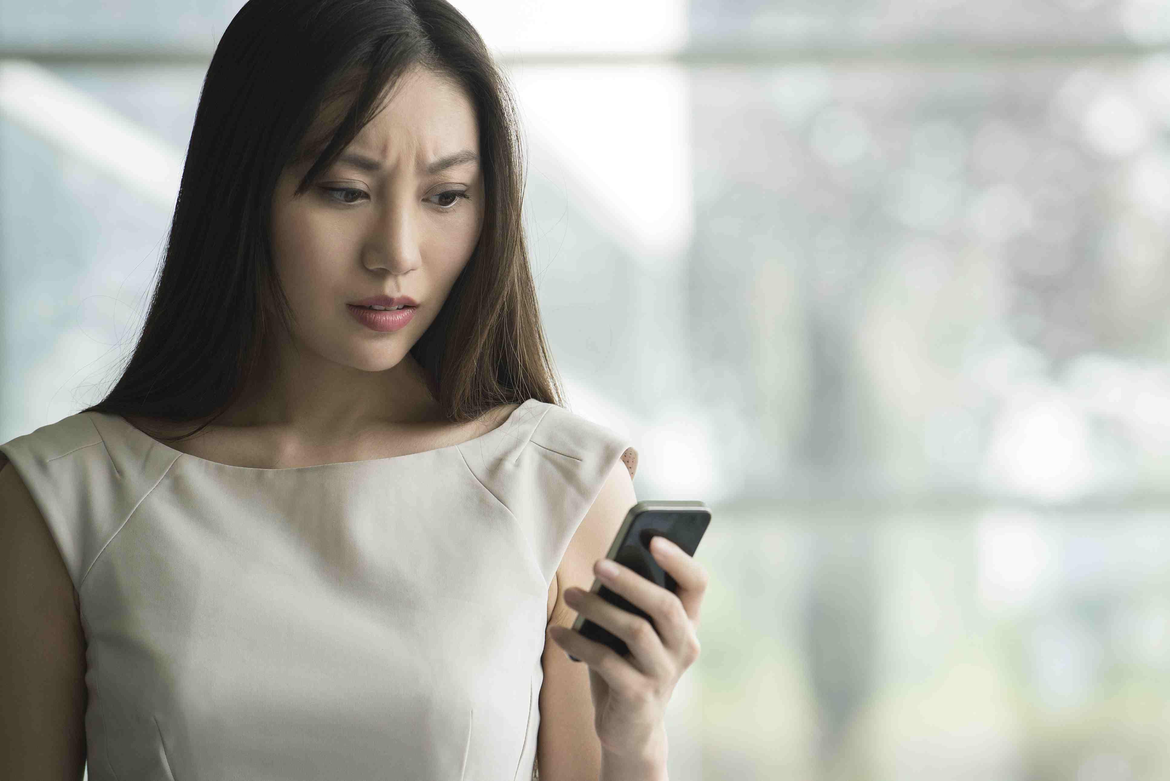Woman receiving bad news on smartphone