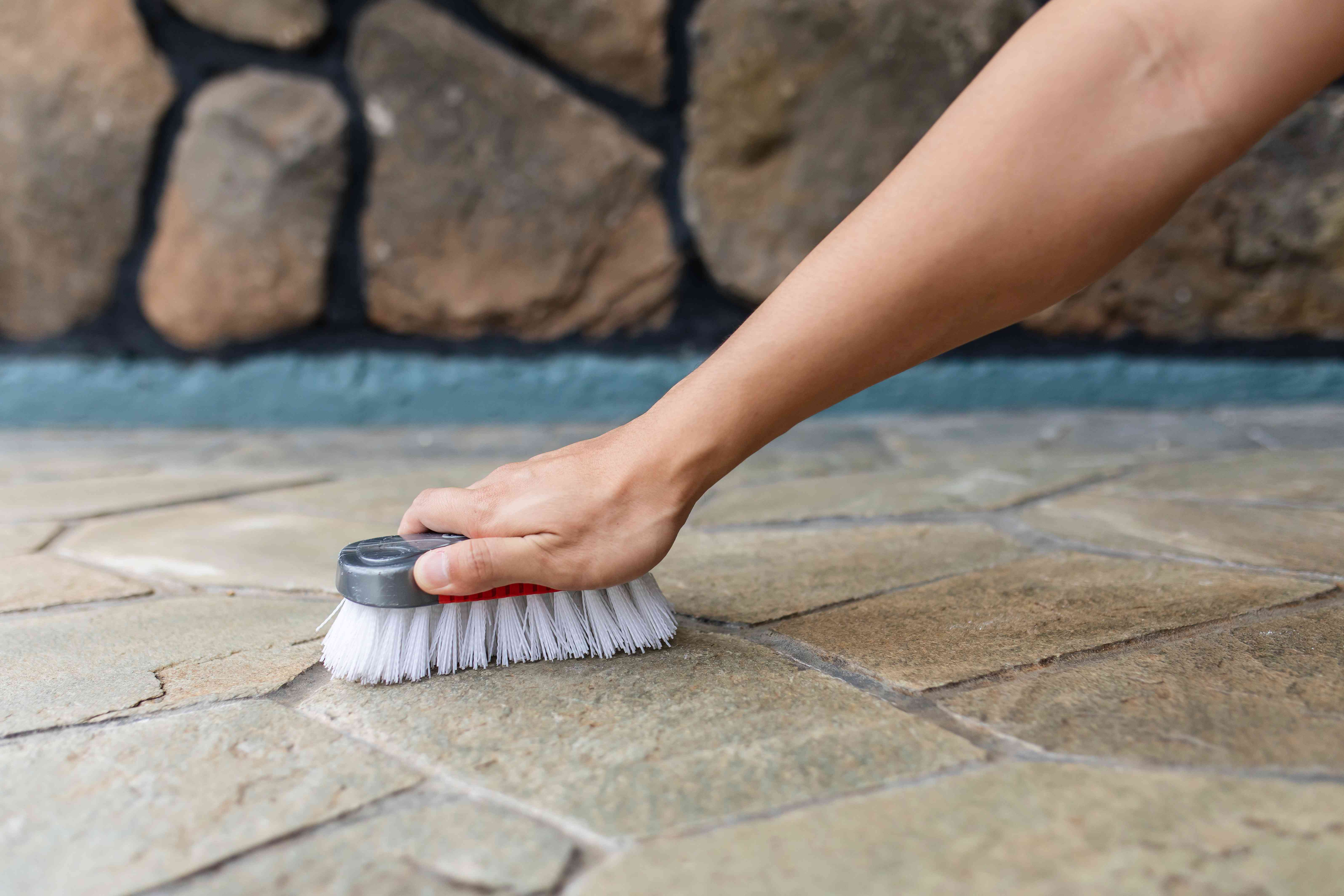 person scrubbing a natural stone floor