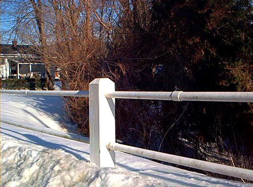 Picture of a post-and-rail fence using a metal rail.