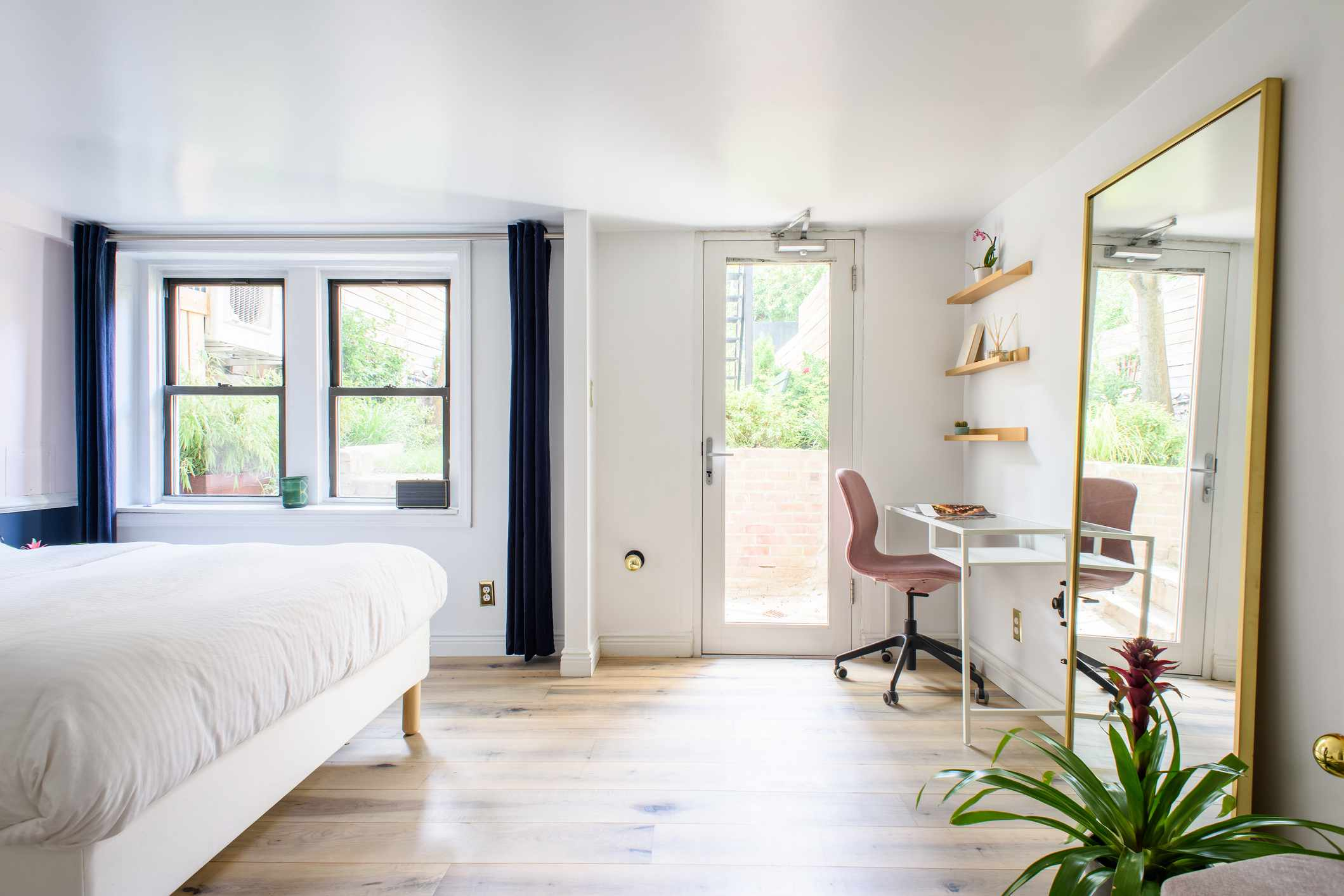 A full-length mirror in a bright bedroom