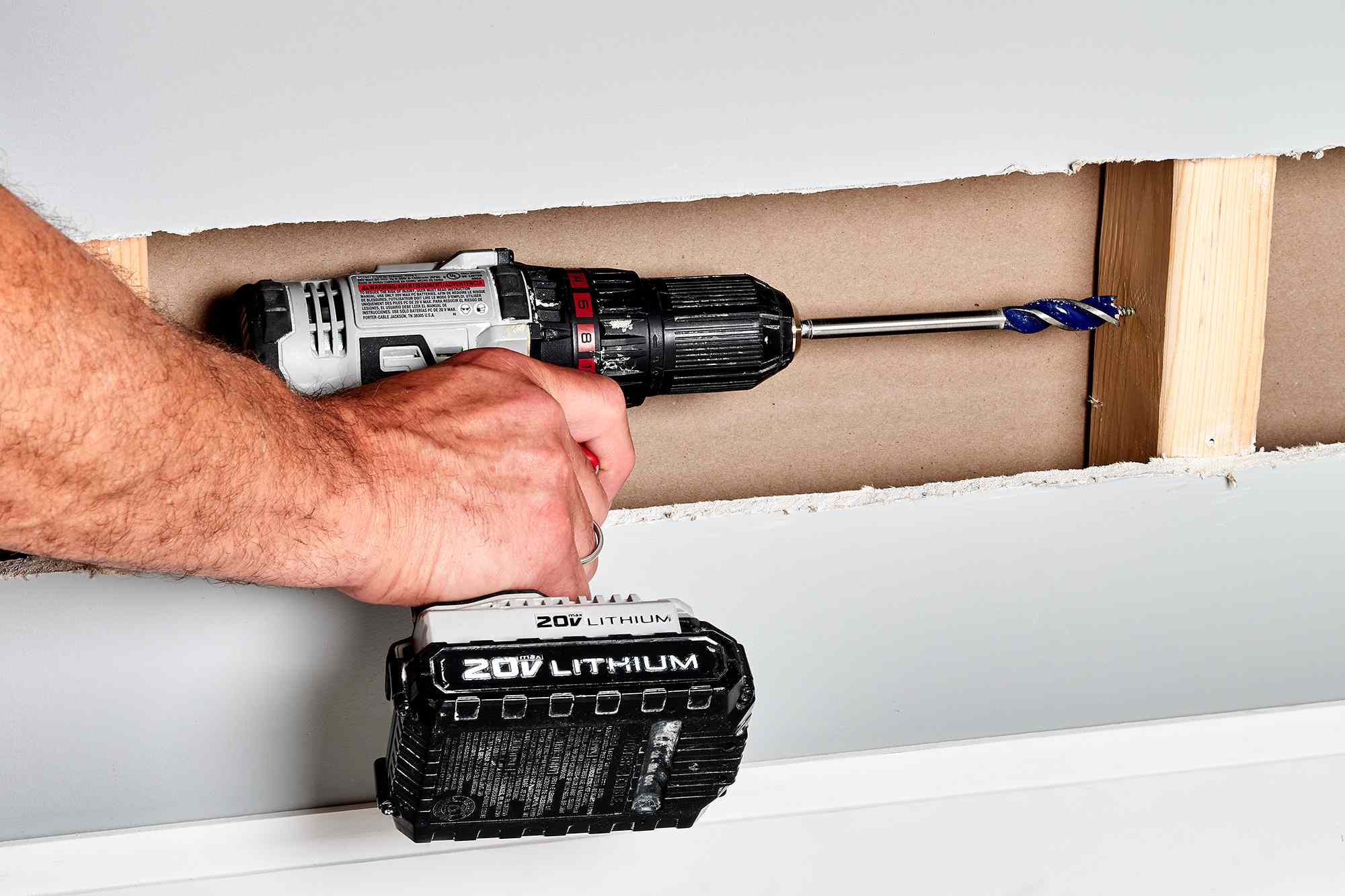 Drill driving holes in wall studs for the electrical wire to run through