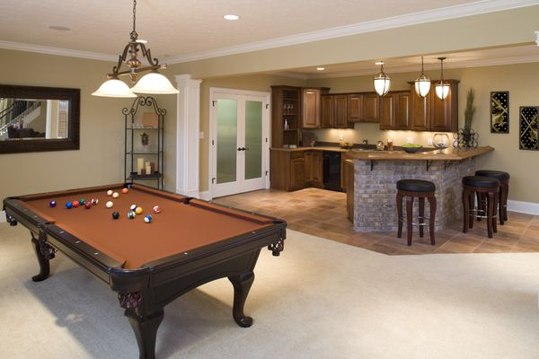Basement rec room with carpet and bar area.