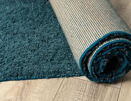 Blue runner rug half rolled and half unrolled on wood floor.