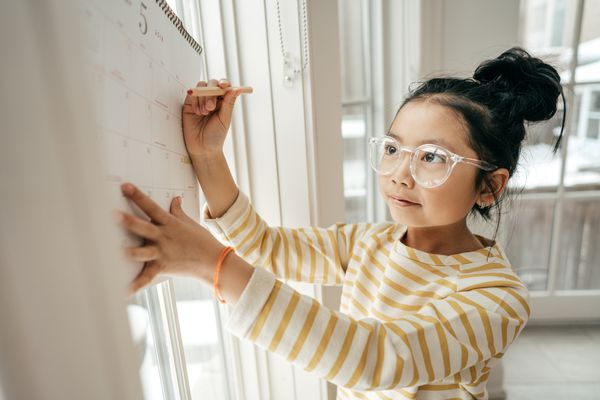child writing on wall calendar