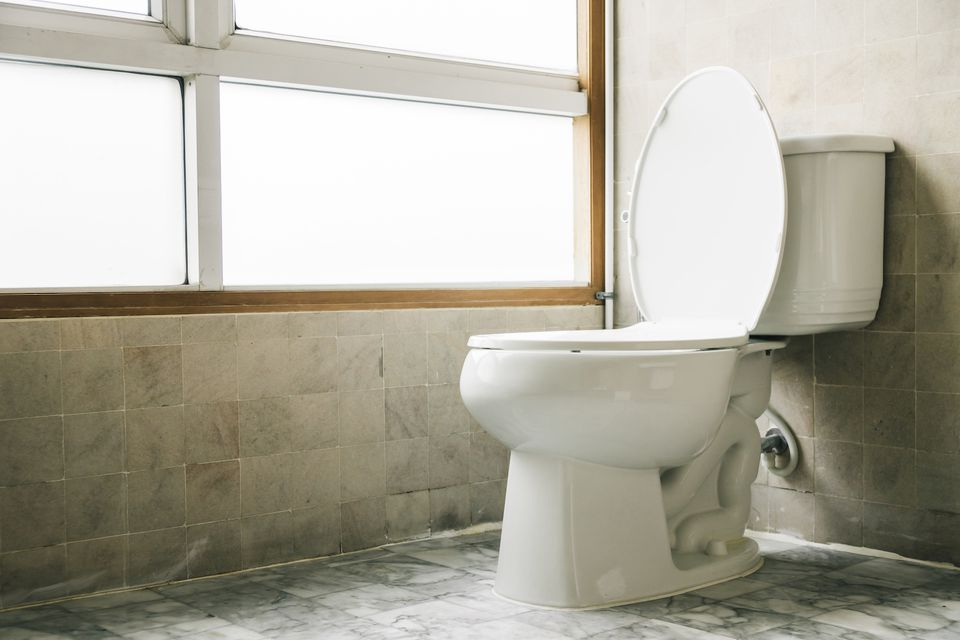 Toilet next to a window in a neutral tiled bathroom