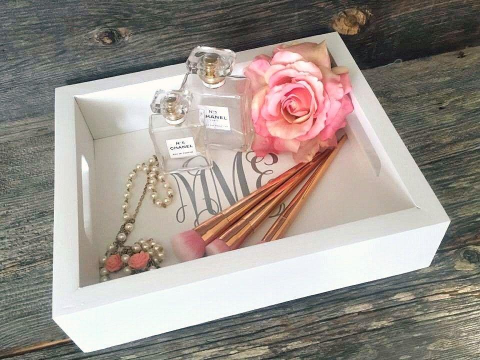 bandeja blanca con pinceles de maquillaje, perfume, un collar y una flor