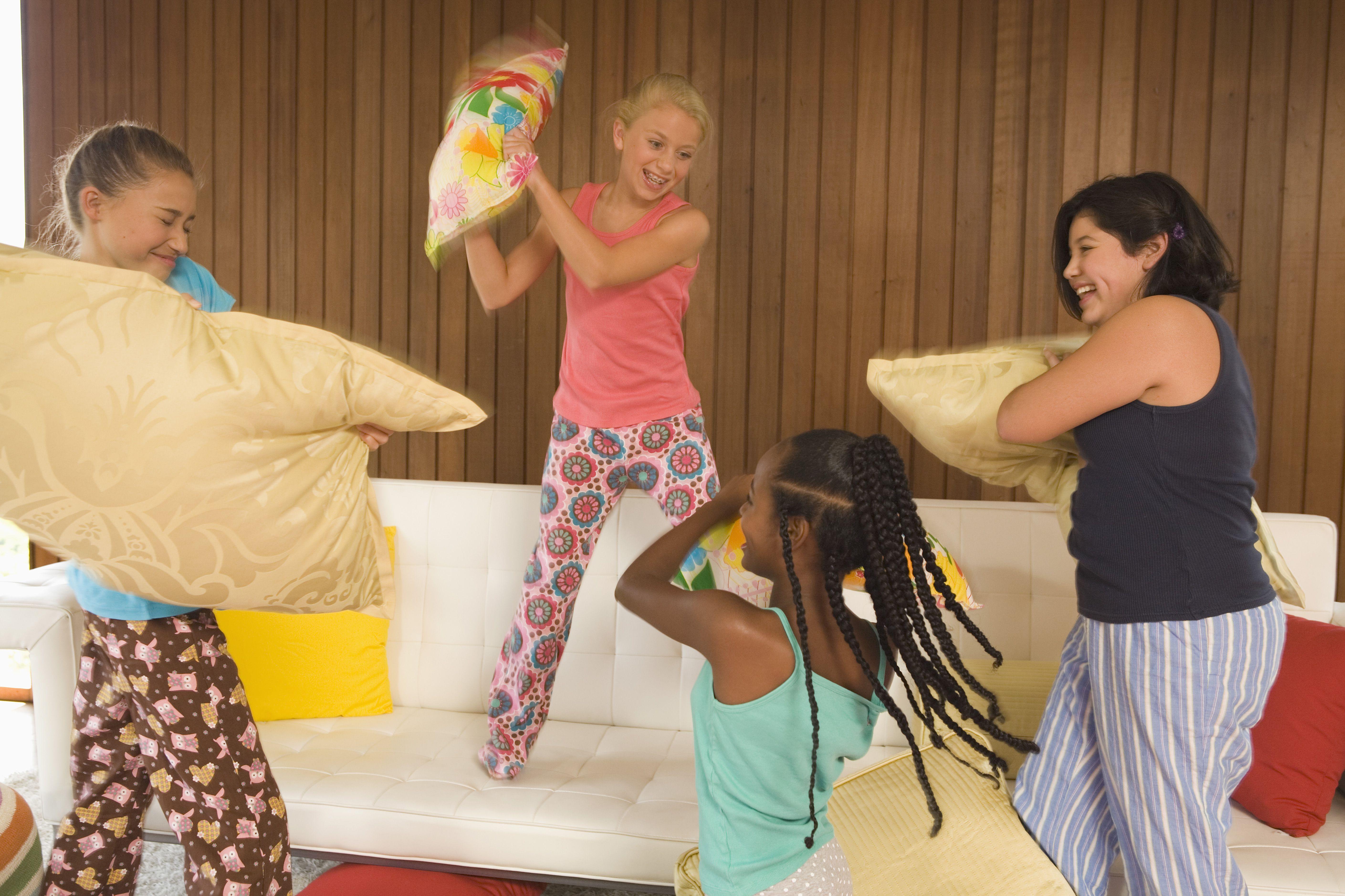 Pre-teen girls having a pillow fight