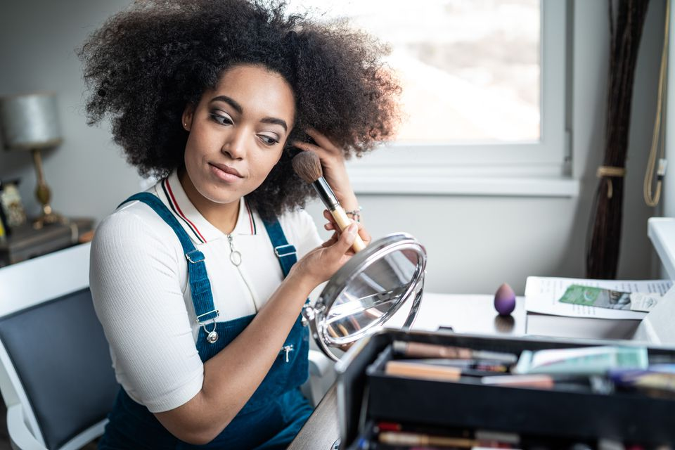 Young woman applying an assortment of makeup on at home