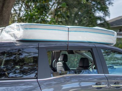 mattress secured to the roof of a car