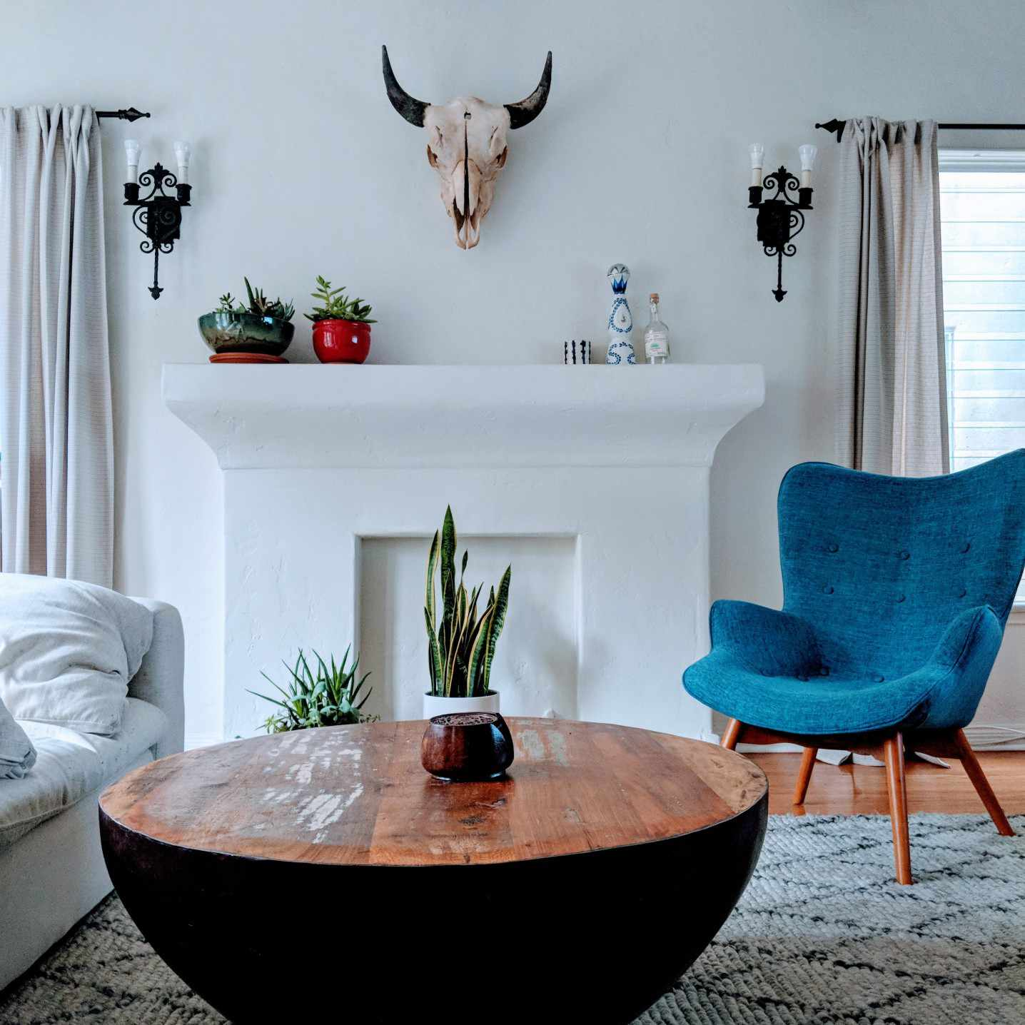 Boho chic living room with circular table, blue chair, faux fireplace, and bull head on the wall.