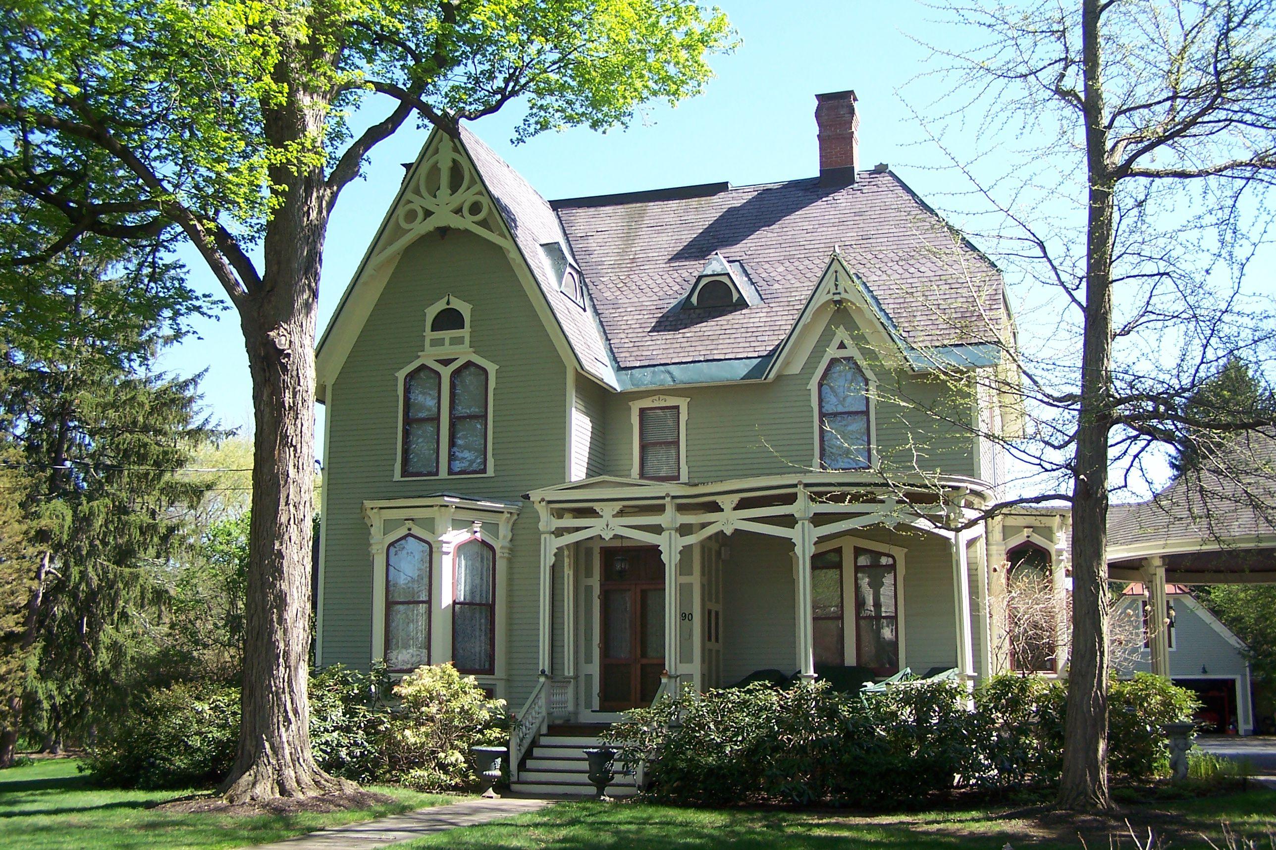 Casa victoriana de dos pisos con techos empinados con frontones y adornos de bargeboard