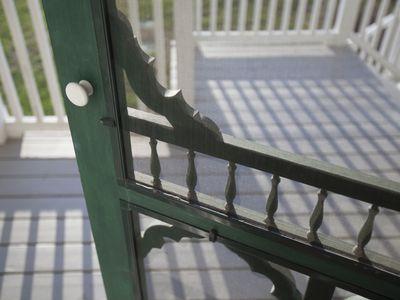 A close up shot of a screen door swinging open onto a sunny porch