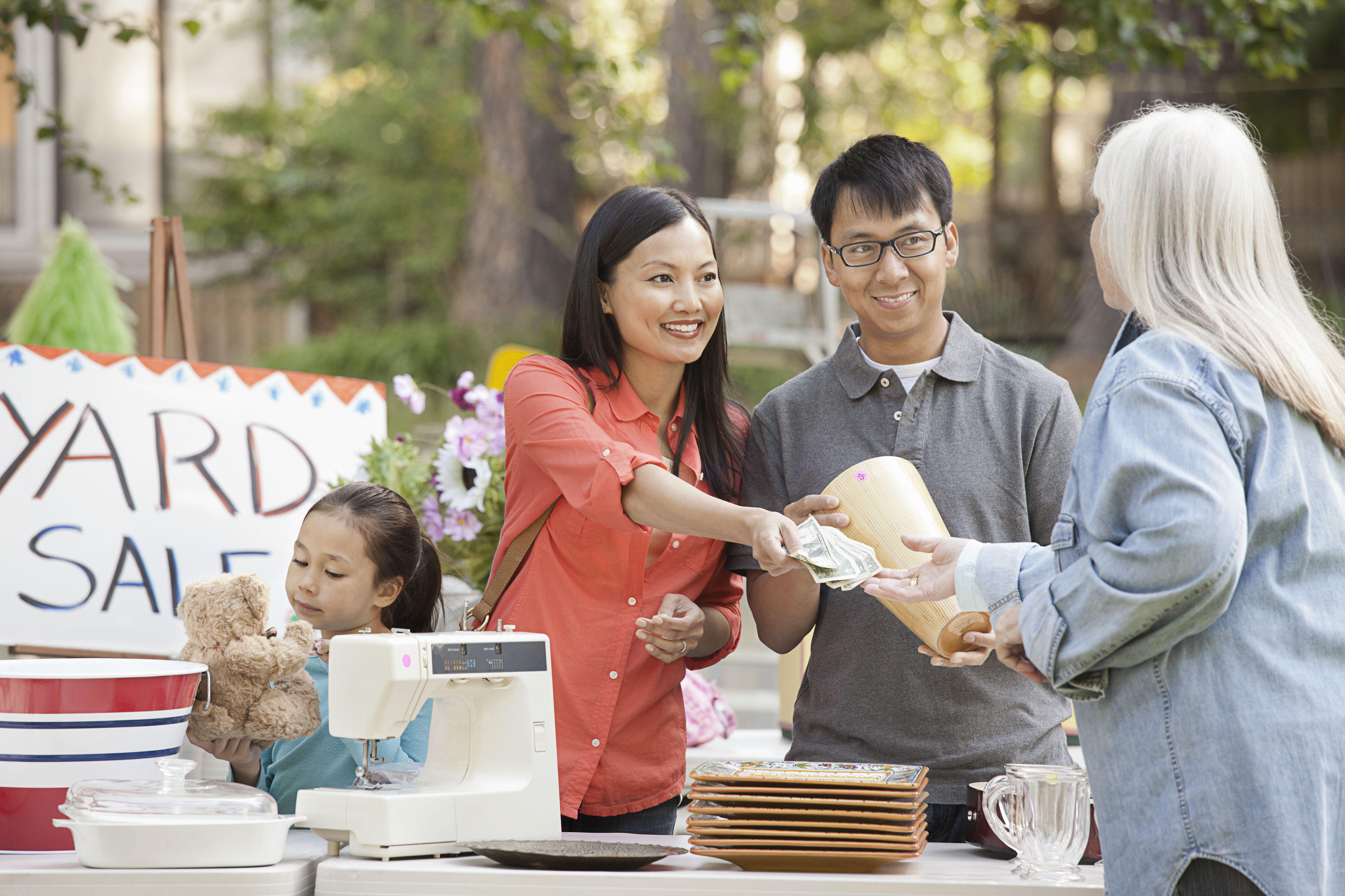Familia asiática comprando en venta de garaje