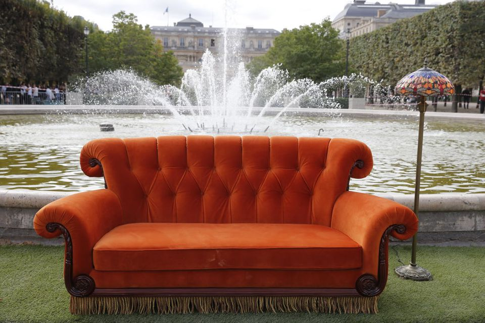 Famous couch from Friends outside in front of a fountain next to a lamp