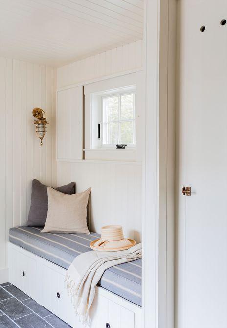 banco de barro pequeño debajo de una ventana en una cabaña blanca