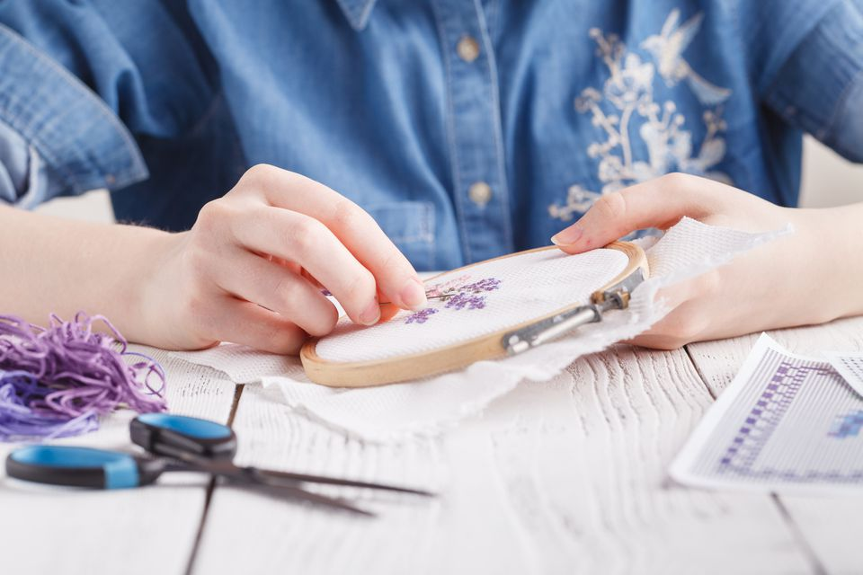 Hands embroidering a flower. Cross-Stitch.