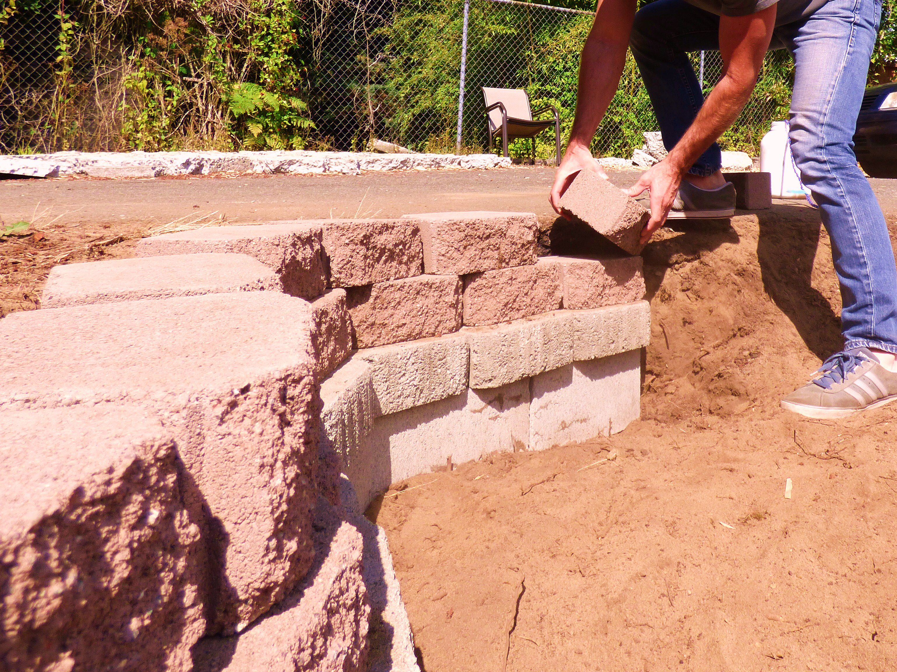 Man shoring up the pond walls with retaining wall block