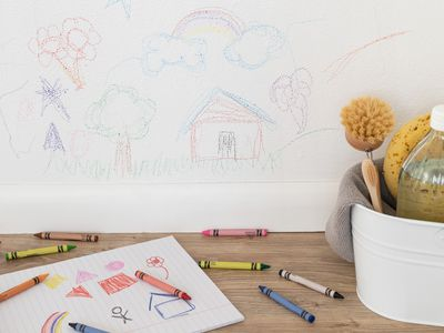 Wax crayon drawings on white painted wall next to cleaning supplies, crayons and paper drawing