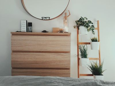 bedroom with white walls, plants, circle mirror, and gray bedding