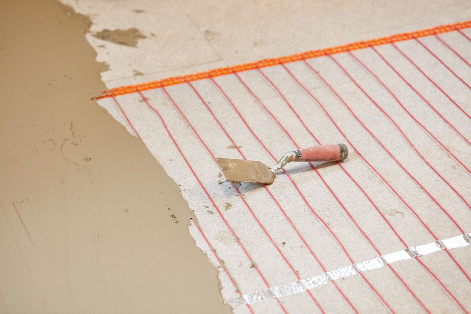 Electric radiant floor heating system with orange wires covered partially by thin-set mortar and scraper