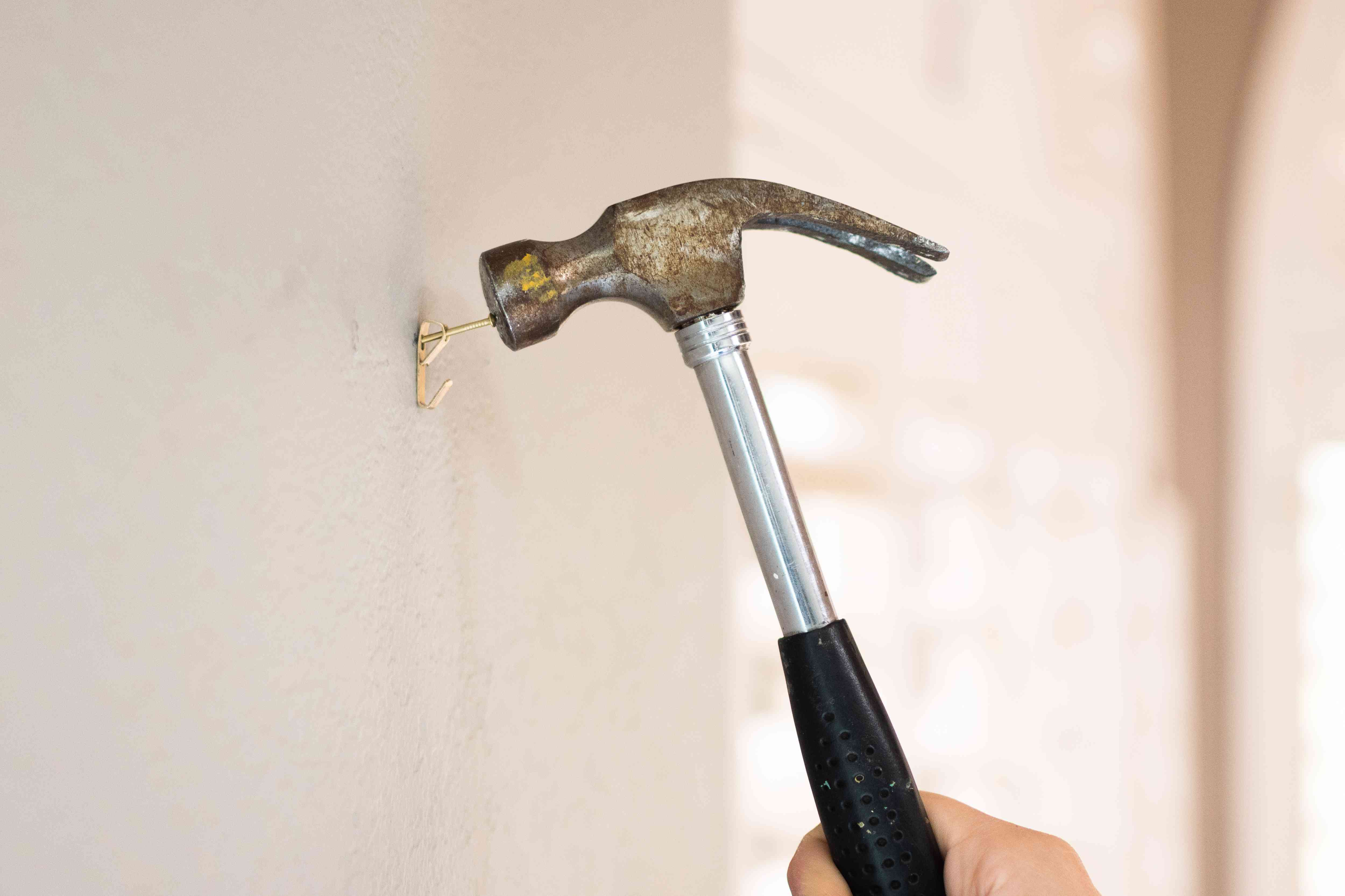 Hammer tapping nail on wall to place bottom of sawtooth hanger