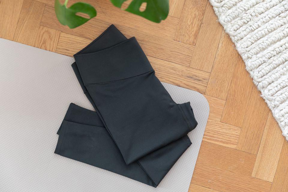 Dark yoga pants folded on a yoga mat on a wooden floor