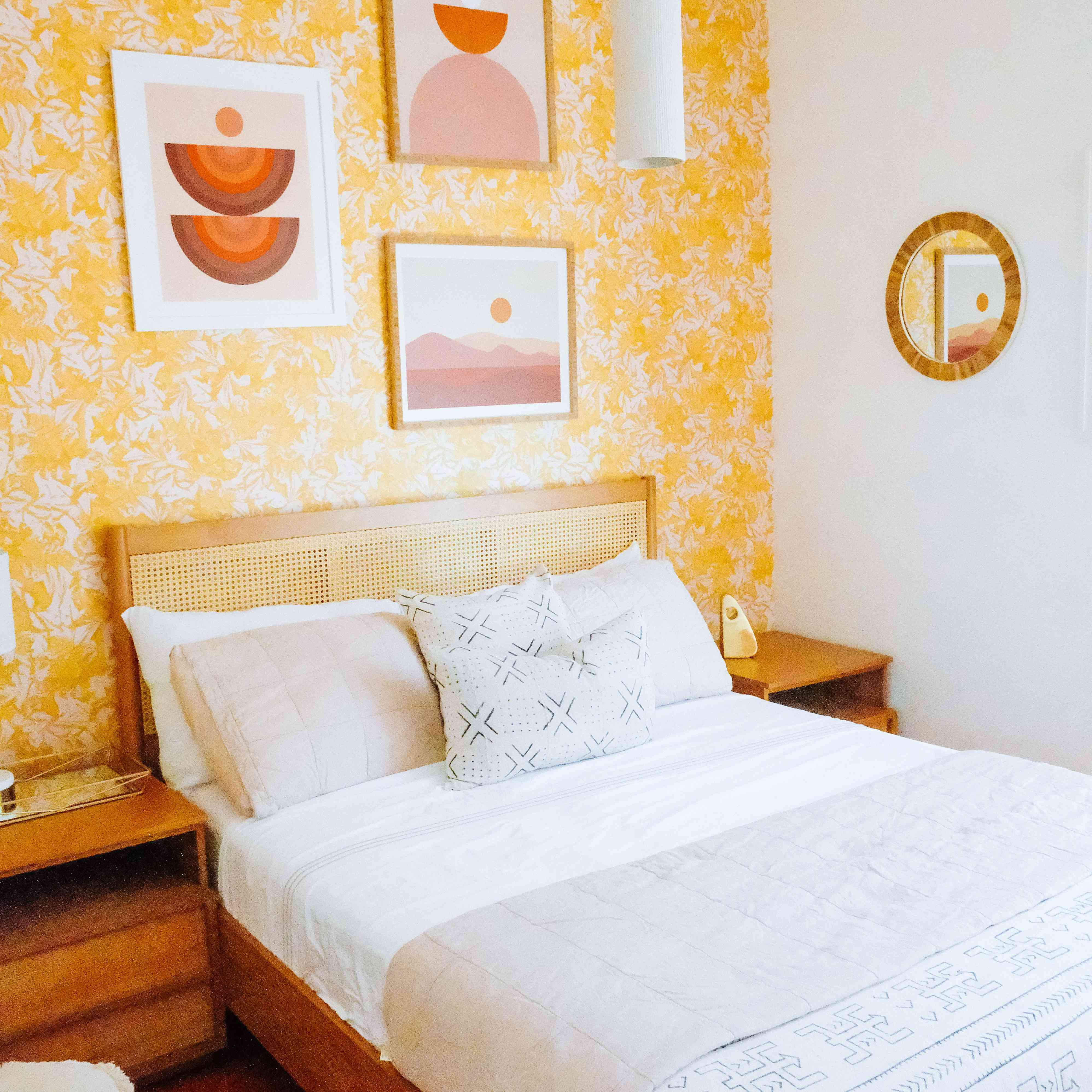 bedroom with floral yellow wallpaper, accented with red and orange tones, wicker and wood furniture