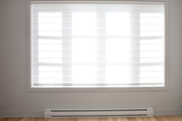 Large residential window with baseboard heating and wooden floors