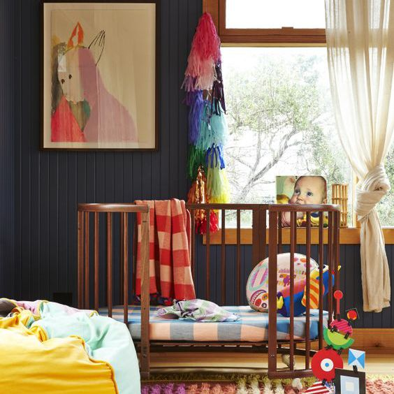 Gender-neutral nursery with black walls and bright accents