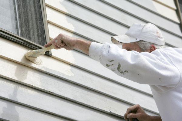 A house painter works around the window trim