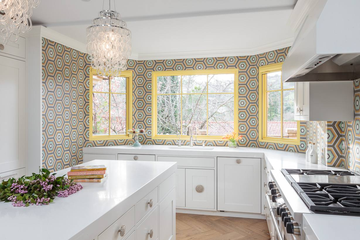 El azulejo colorido crea una pared característica en una cocina blanca