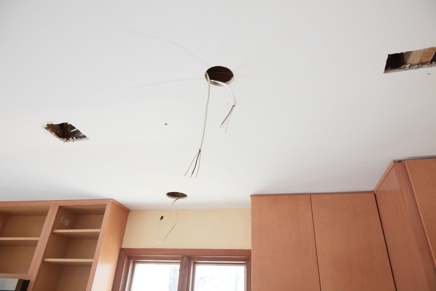 Ceiling with exposed recessed lighting holes and wires hanging