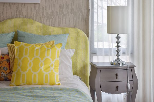 bedroom with yellow headboard and pillow