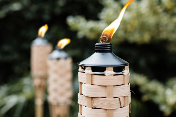 Citronella tiki torches with fire lit to keep mosquitos away closeup