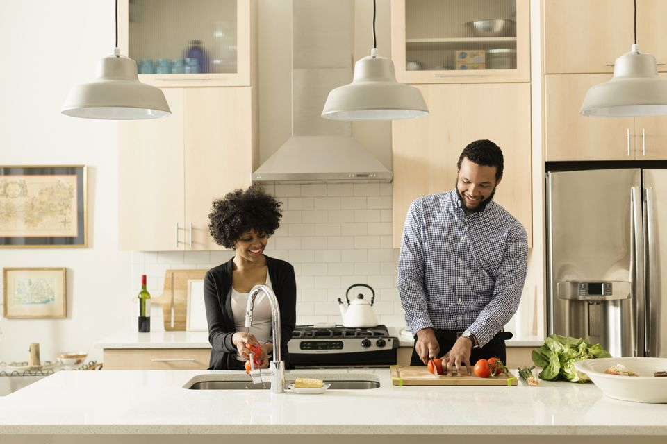 Couple cooking together in clean kitchen