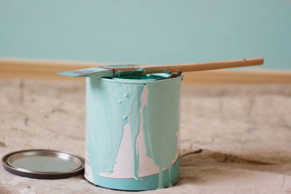 Can of aqua paint and a paint brush in front of a blue wall
