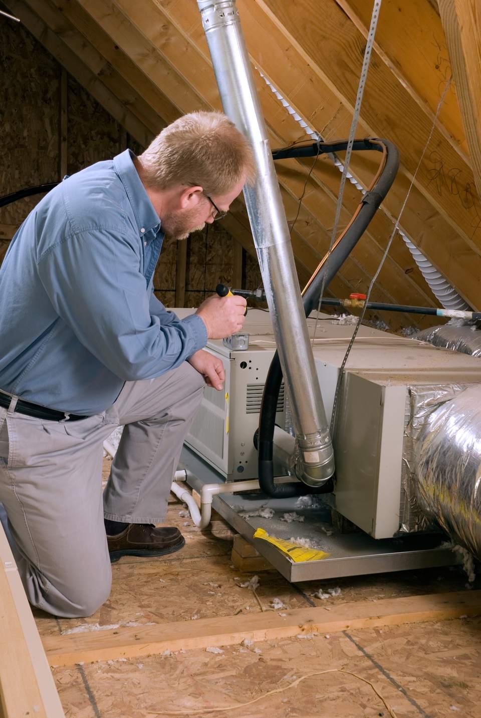 A service expert inspects a furnace