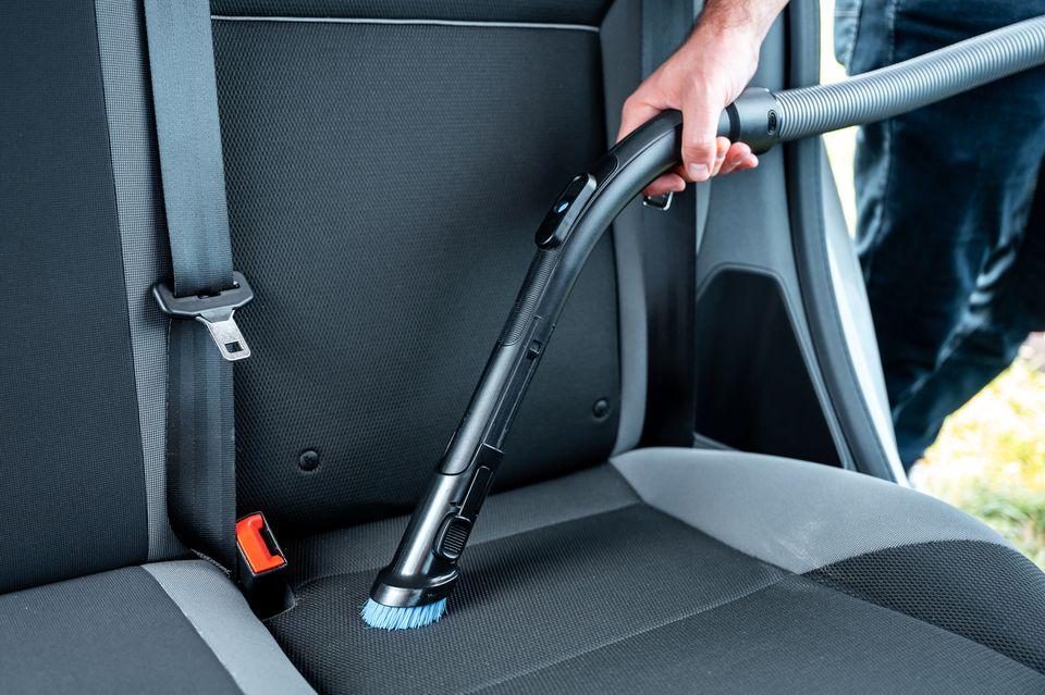 person vacuuming a car seat
