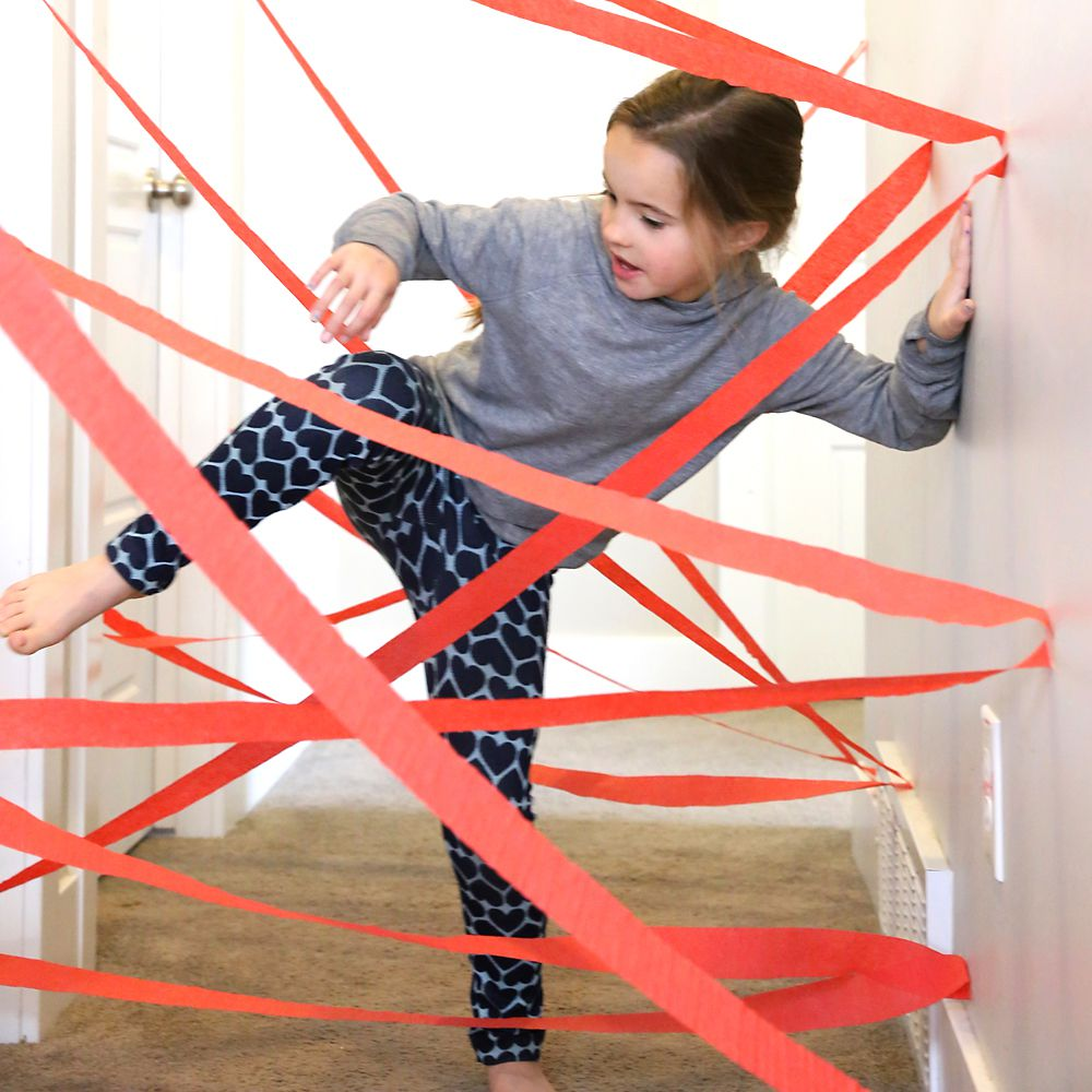 A girl making her way through a crepe paper maze