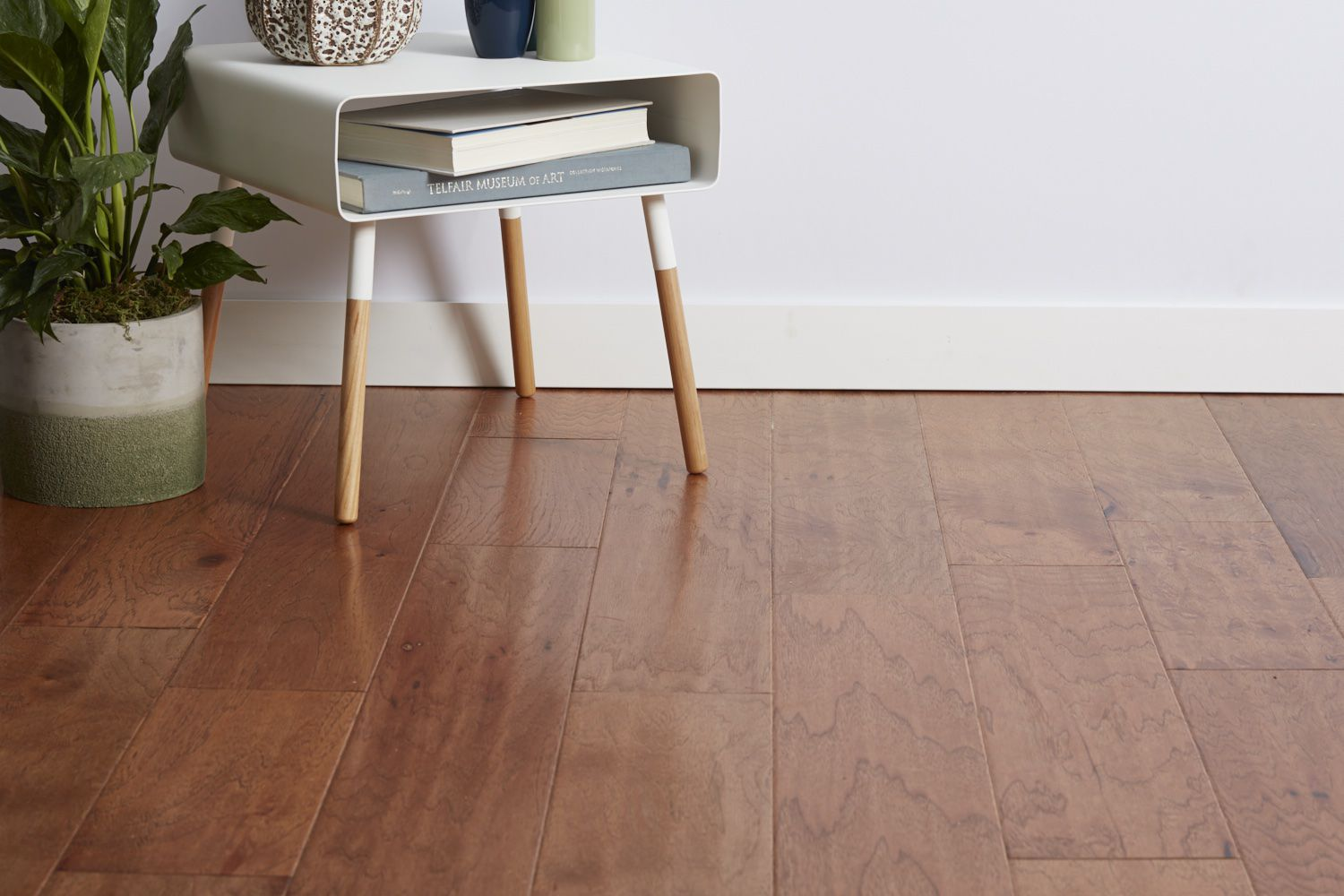 Engineered wood flooring with houseplant and side table with books