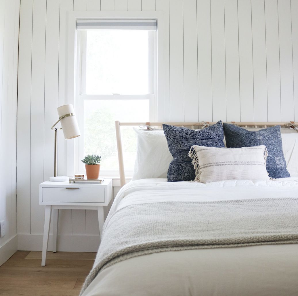 white bedroom with open windows, blue accent pillows on bed