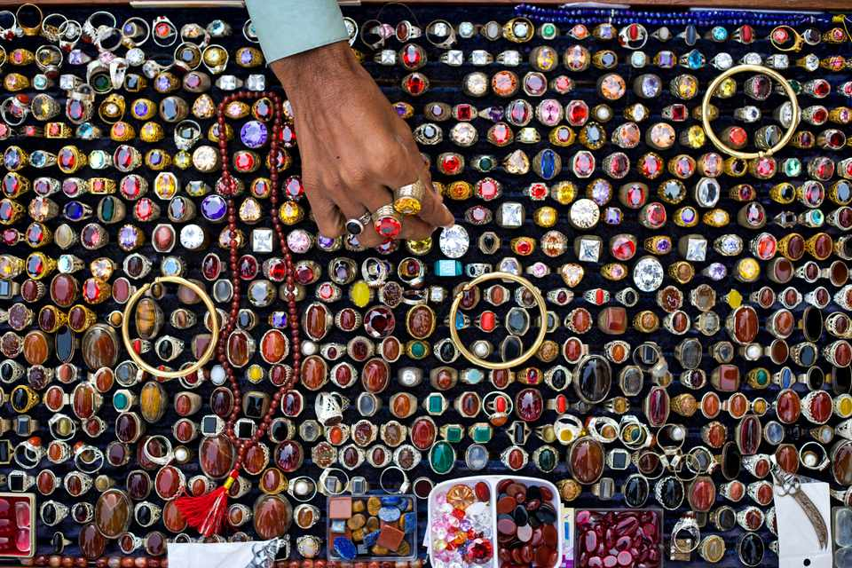 A woman searches for the right ring out of a large selection of precious and semiprecious gemstones