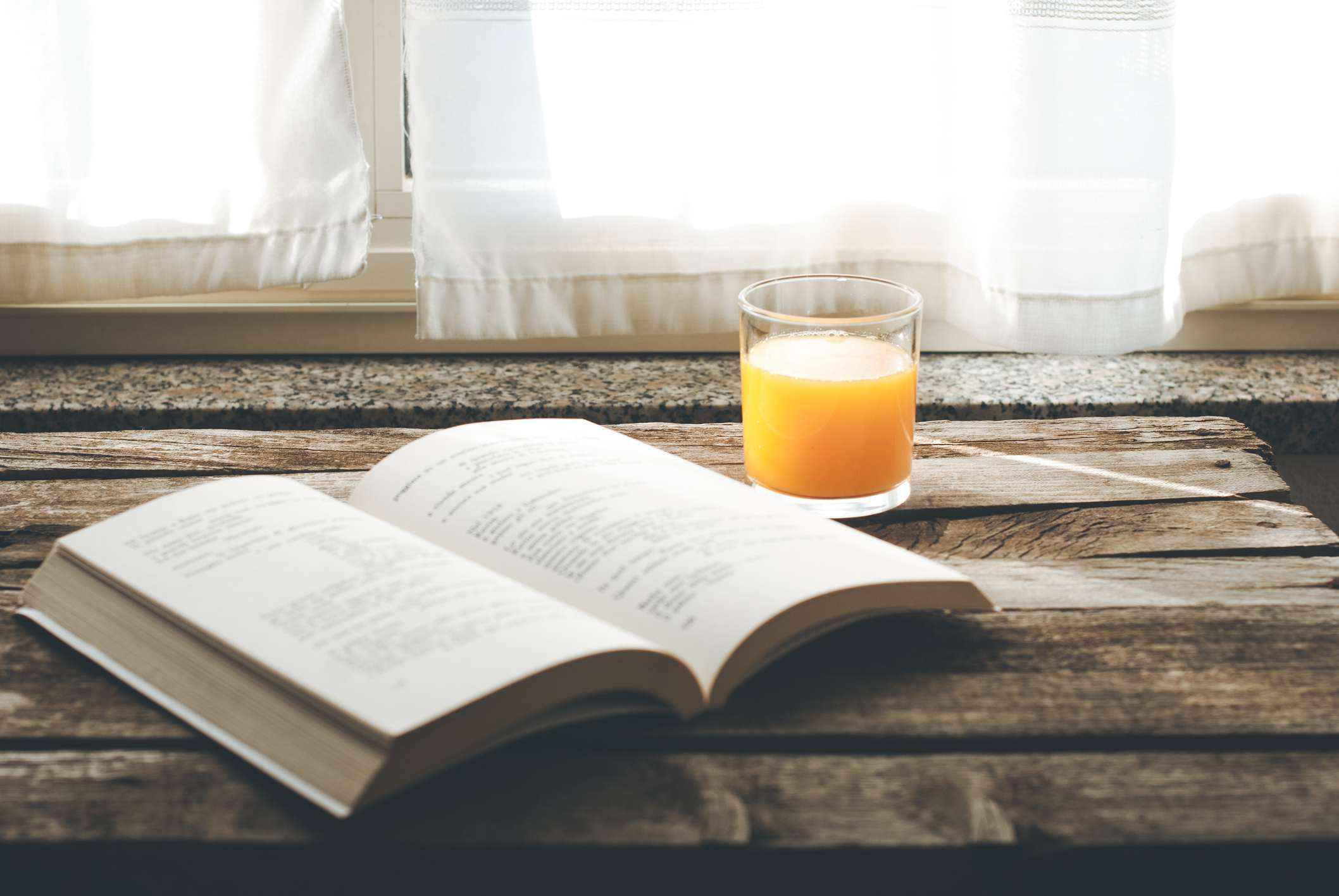 Book on table with orange juice