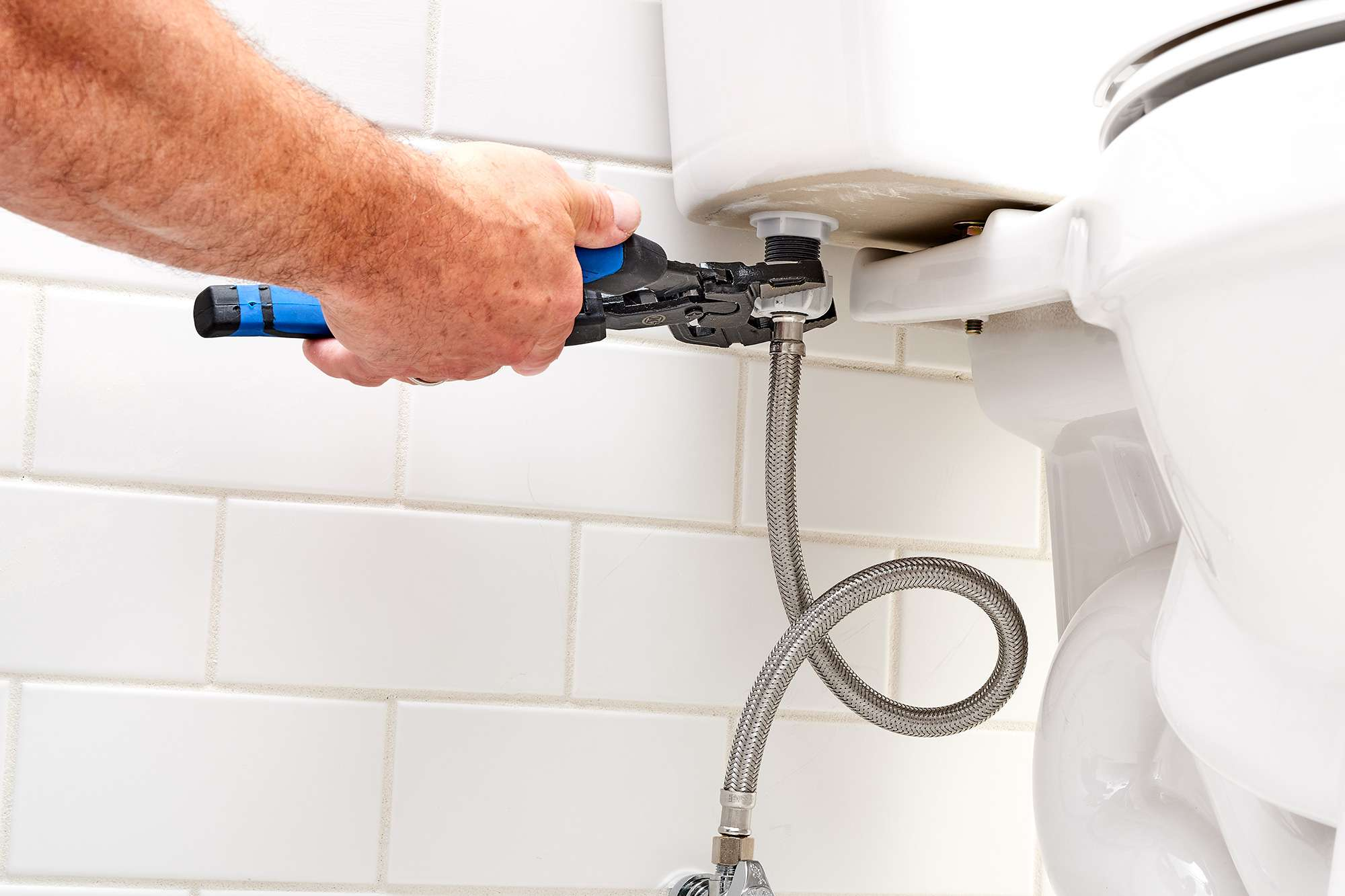 Disconnecting water supply tube with wrench to remove toilet fill valve