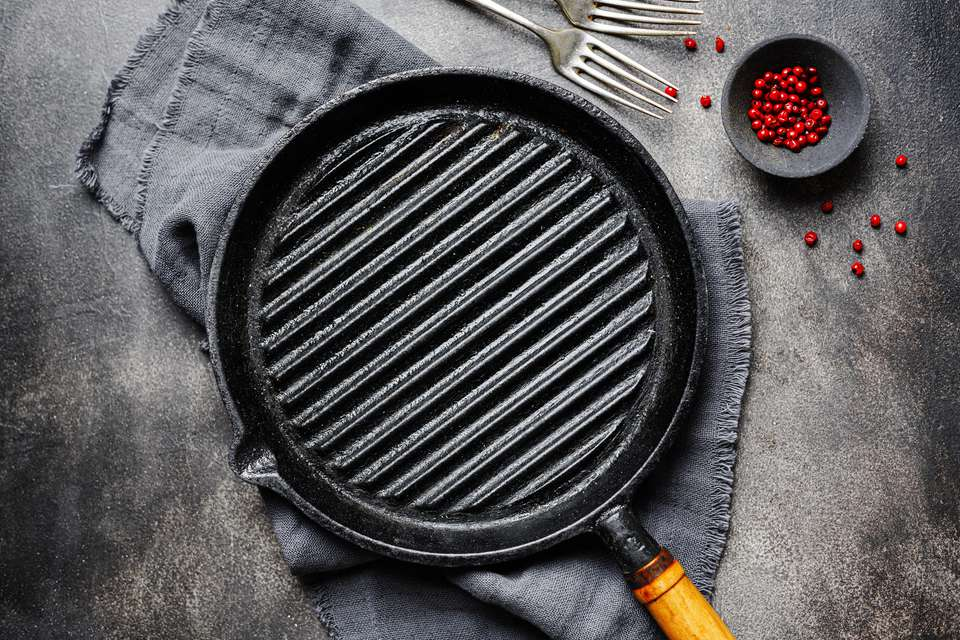 Cast iron griddle pan on grey towel with two forks and red peppercorns