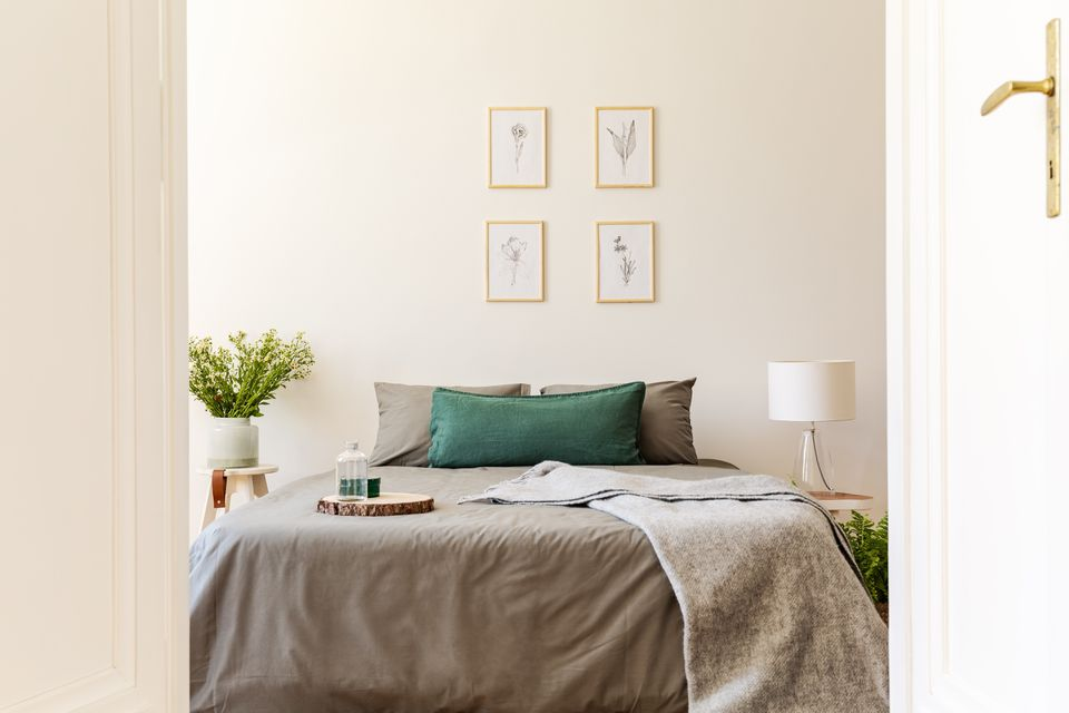 A peek through an open door into a natural sunny bedroom interior with gray and green sheets and cushions on a double bed. Nature drawings on the vanilla wall. Real photo.