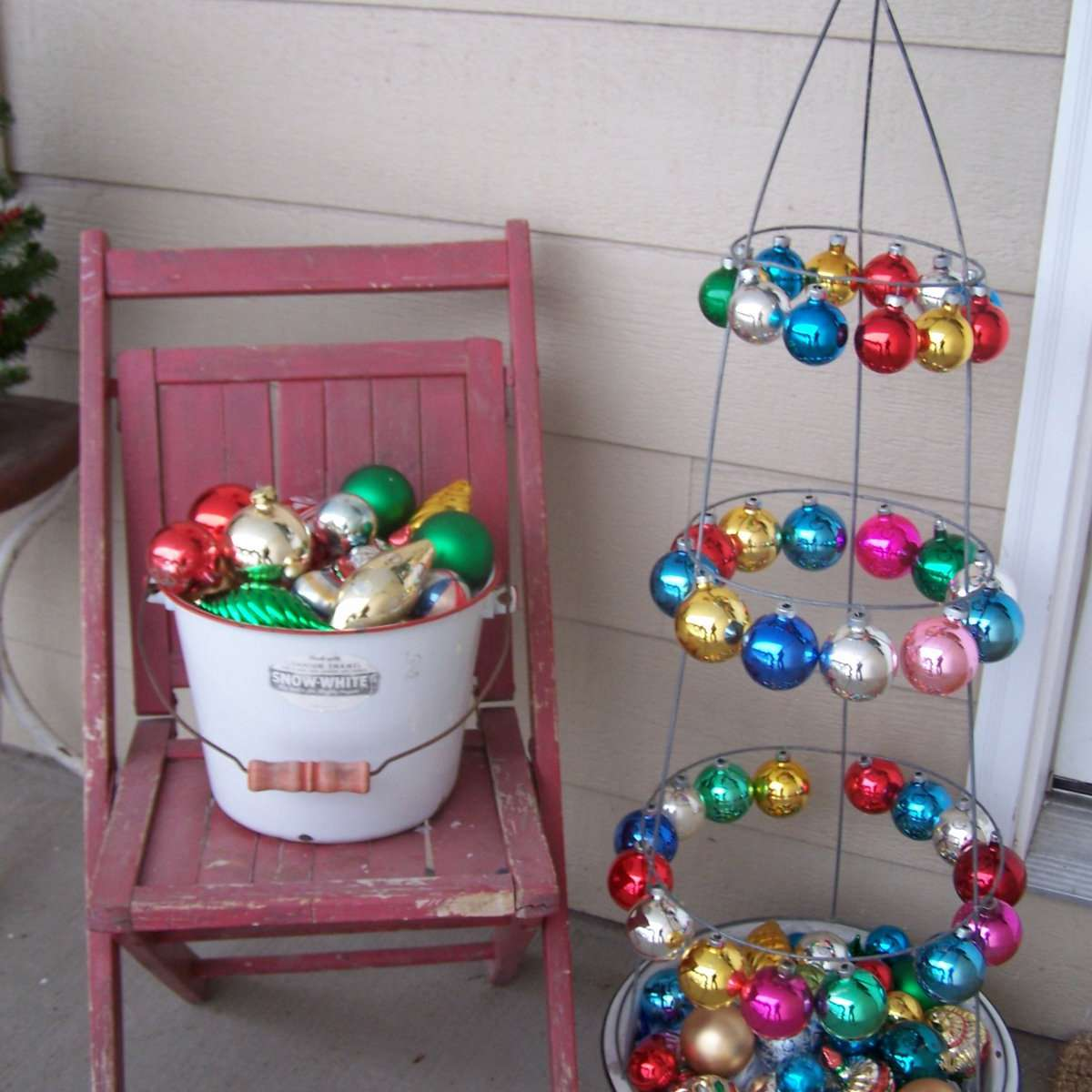 A wire Christmas tree on a porch