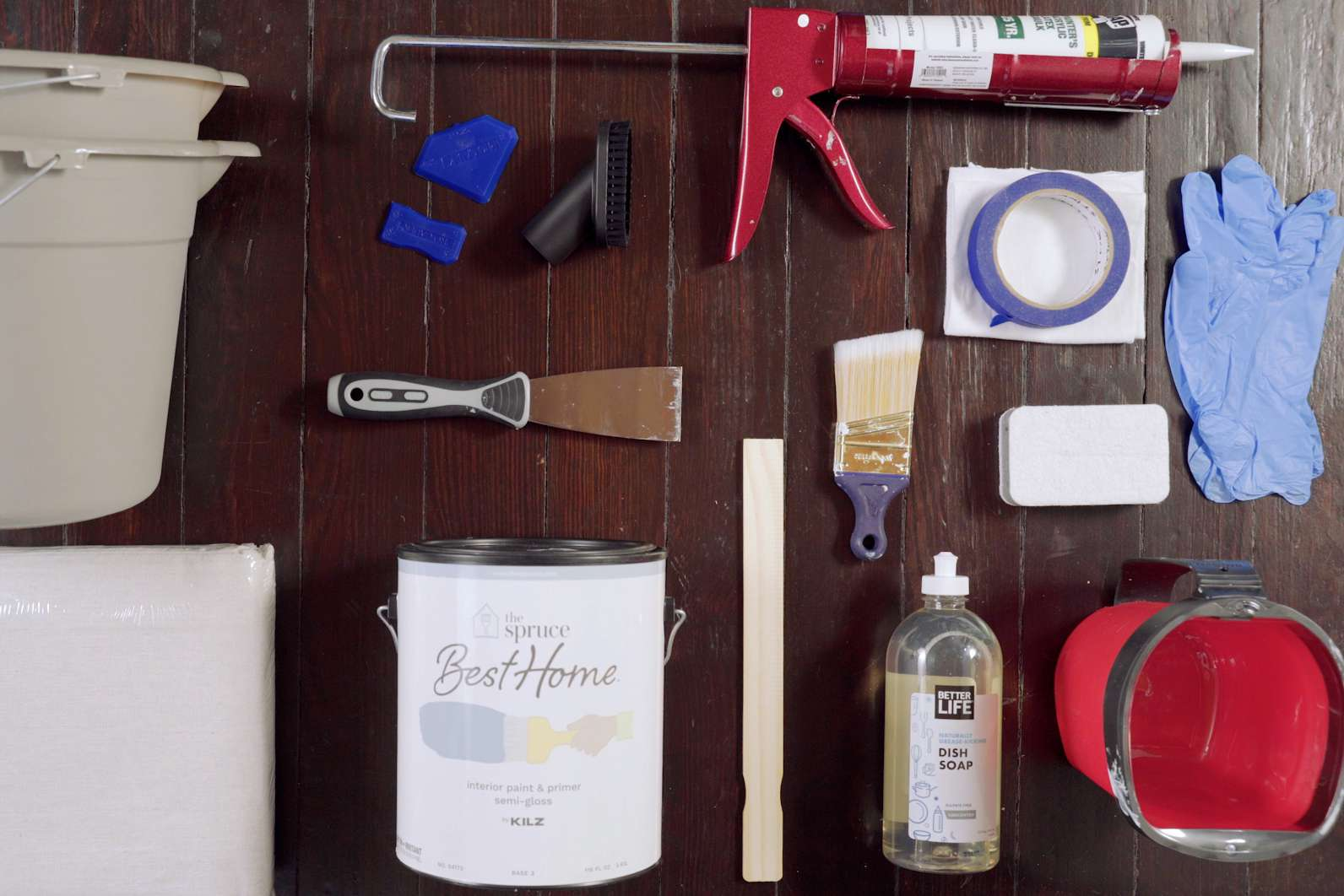 Materials and tools laid on dark brown wooden surface to paint baseboards