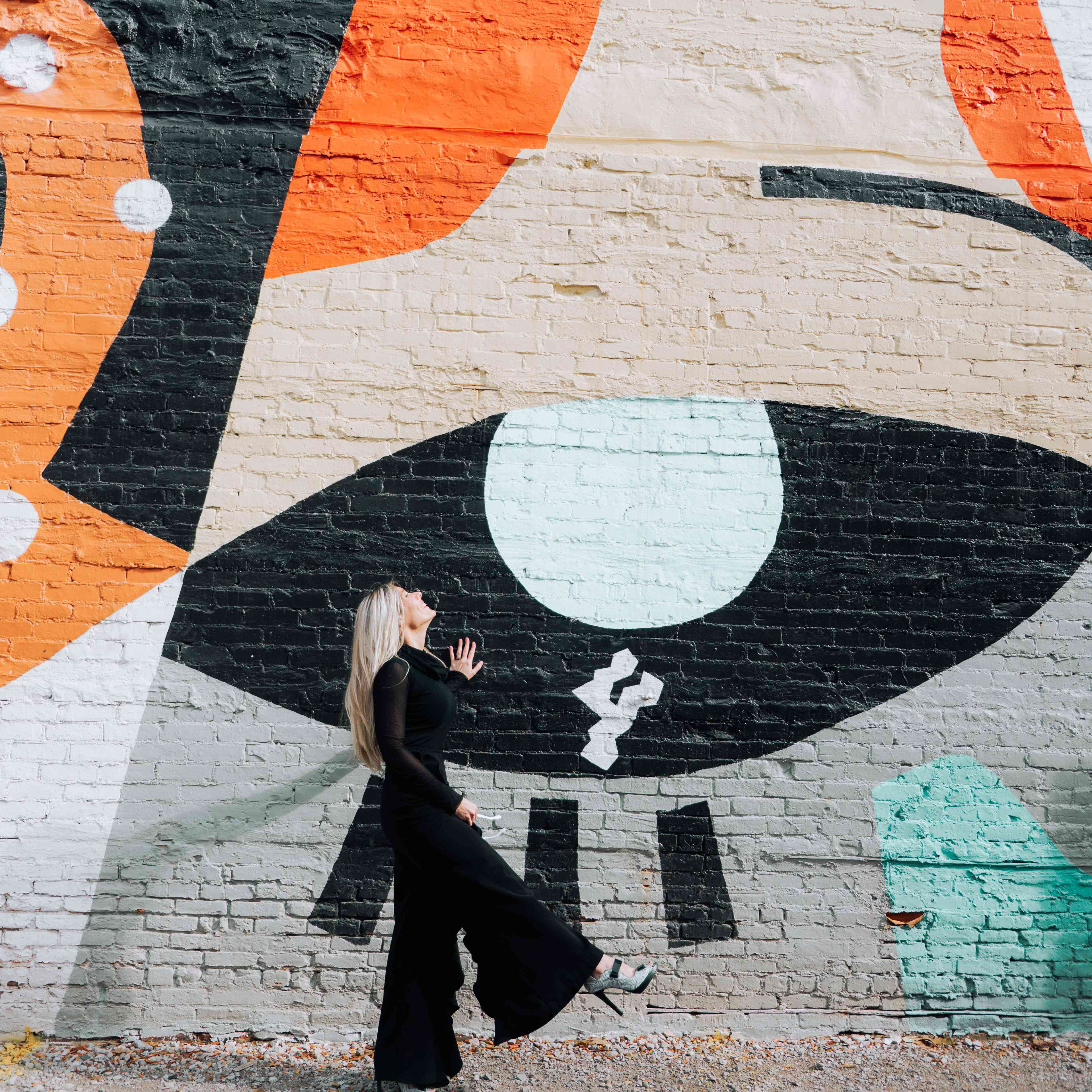 Elin Walters poses in front of a colorful outdoor mural