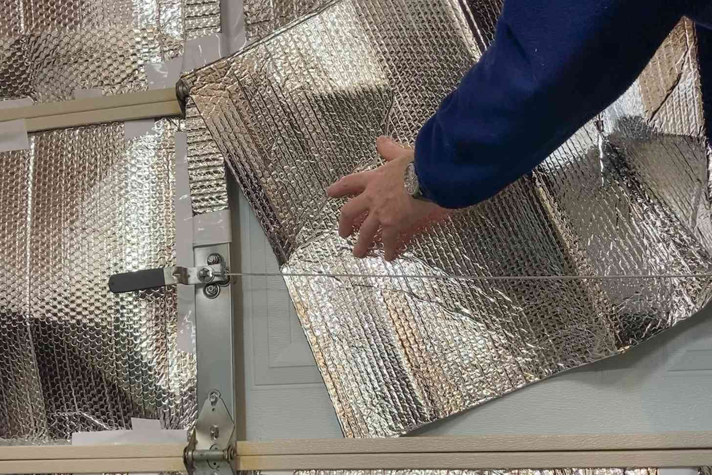 person installing garage door insulation